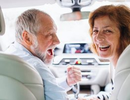 A mature couple in high spirits inside a car