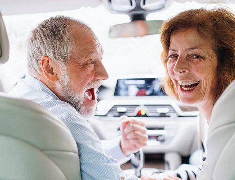 A mature couple in high spirits inside a car
